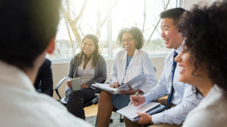 Confident diverse group of hospital administrators sit down to discuss important issues withe hea...