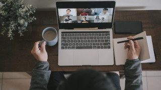 An asian chinese male working at home using laptop video conference call meeting
