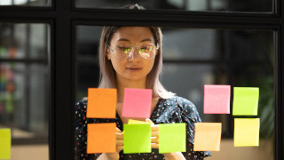 A photo of a focused young woman using sticky post it notes on glass wall.