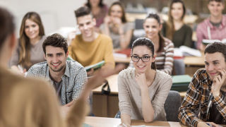 Students smiling at an information session.